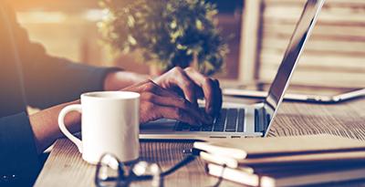 Lönearbete på laptop på skrivbord i massivt trä.